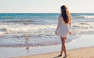 Красивая девушка идет по пляжу
